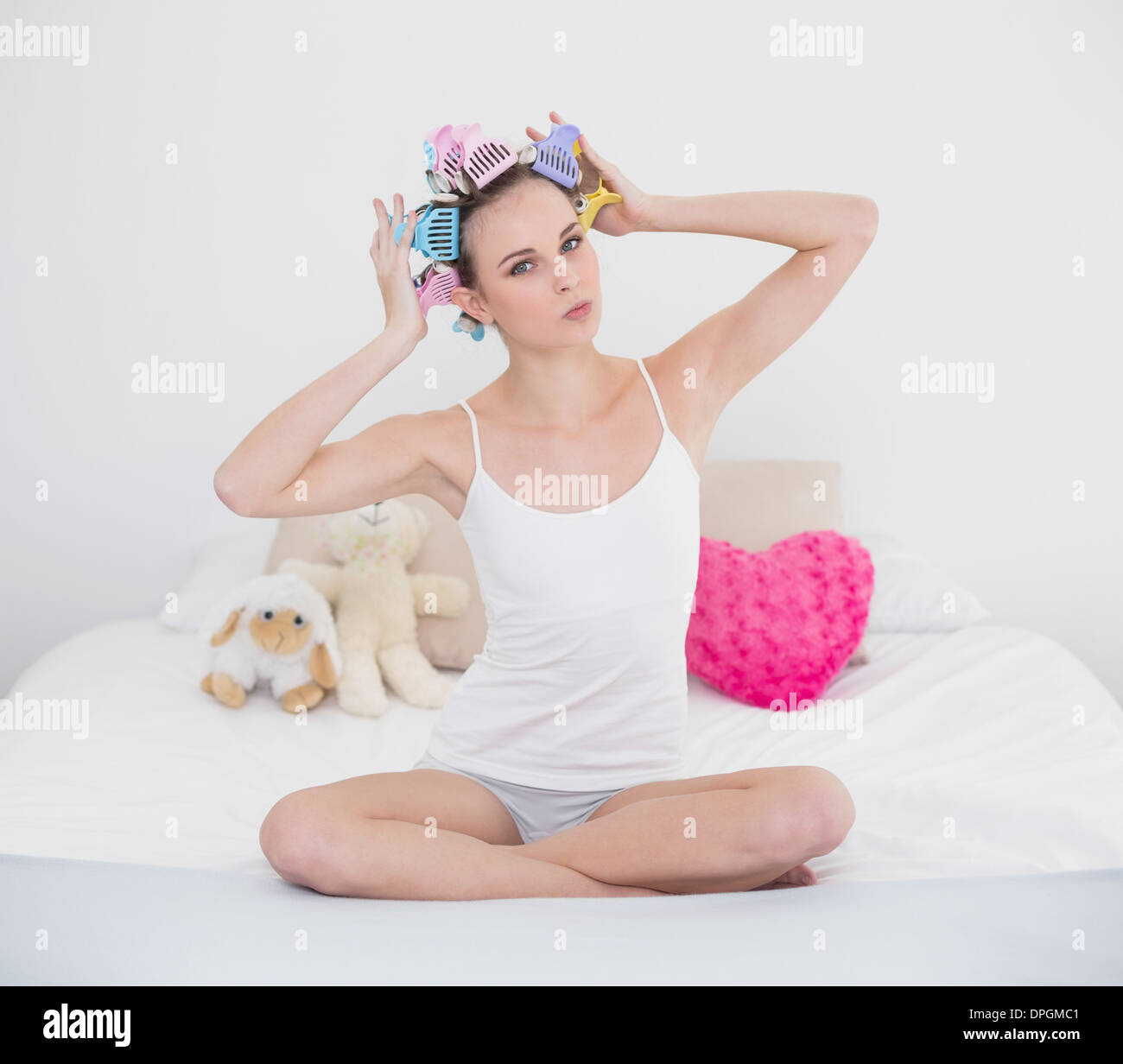 Tacaud natural brown haired woman fixing her hair curlers Photo Stock