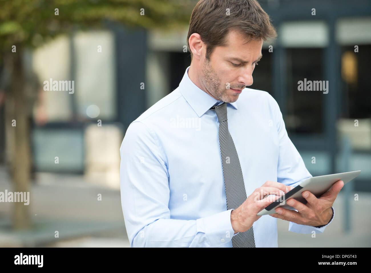 Businessman using digital tablet outdoors Banque D'Images