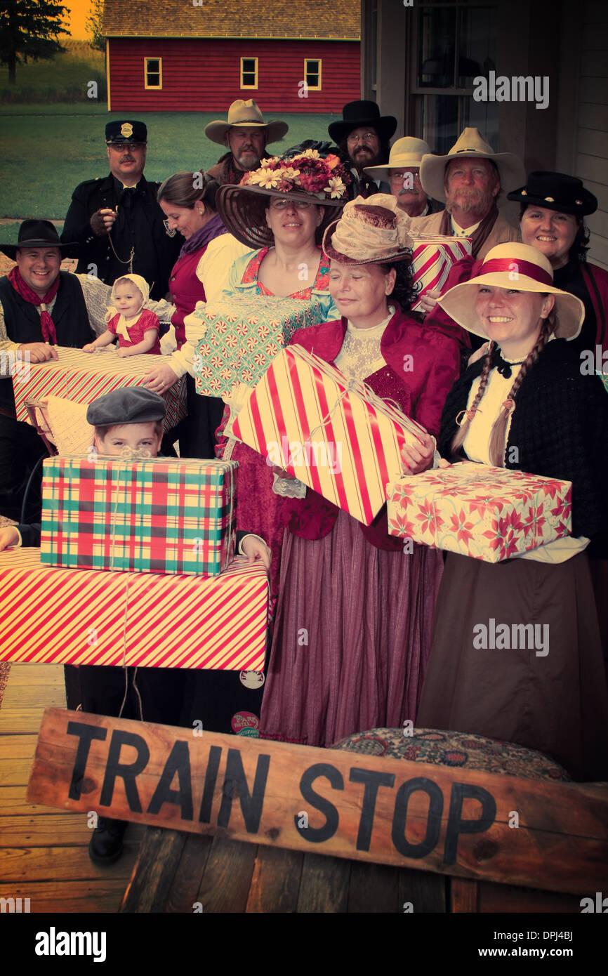 Vintage d'un groupe de personnes à l'ancienne en attente à l'arrêt de train avec des cadeaux de Noël Banque D'Images