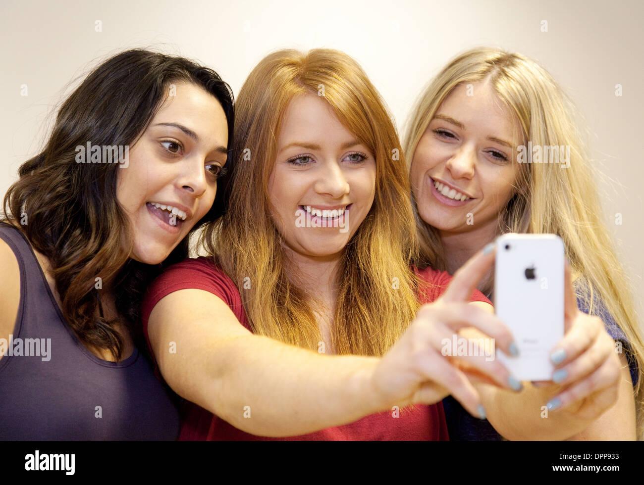 , Selfies prises par trois jeunes femmes adolescents adolescents filles sur un iPhone d'Apple, dans l'Essex, UK Photo Stock