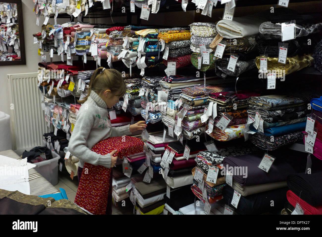 Un enfant regarde par les rouleaux de tissu dans une mercerie shop à Nove Zamky Slovaquie Photo Stock
