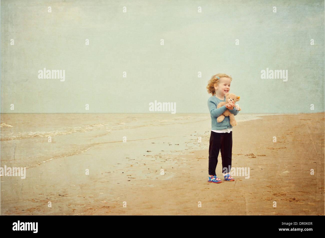 Little girl with teddy bear standing on beach Photo Stock