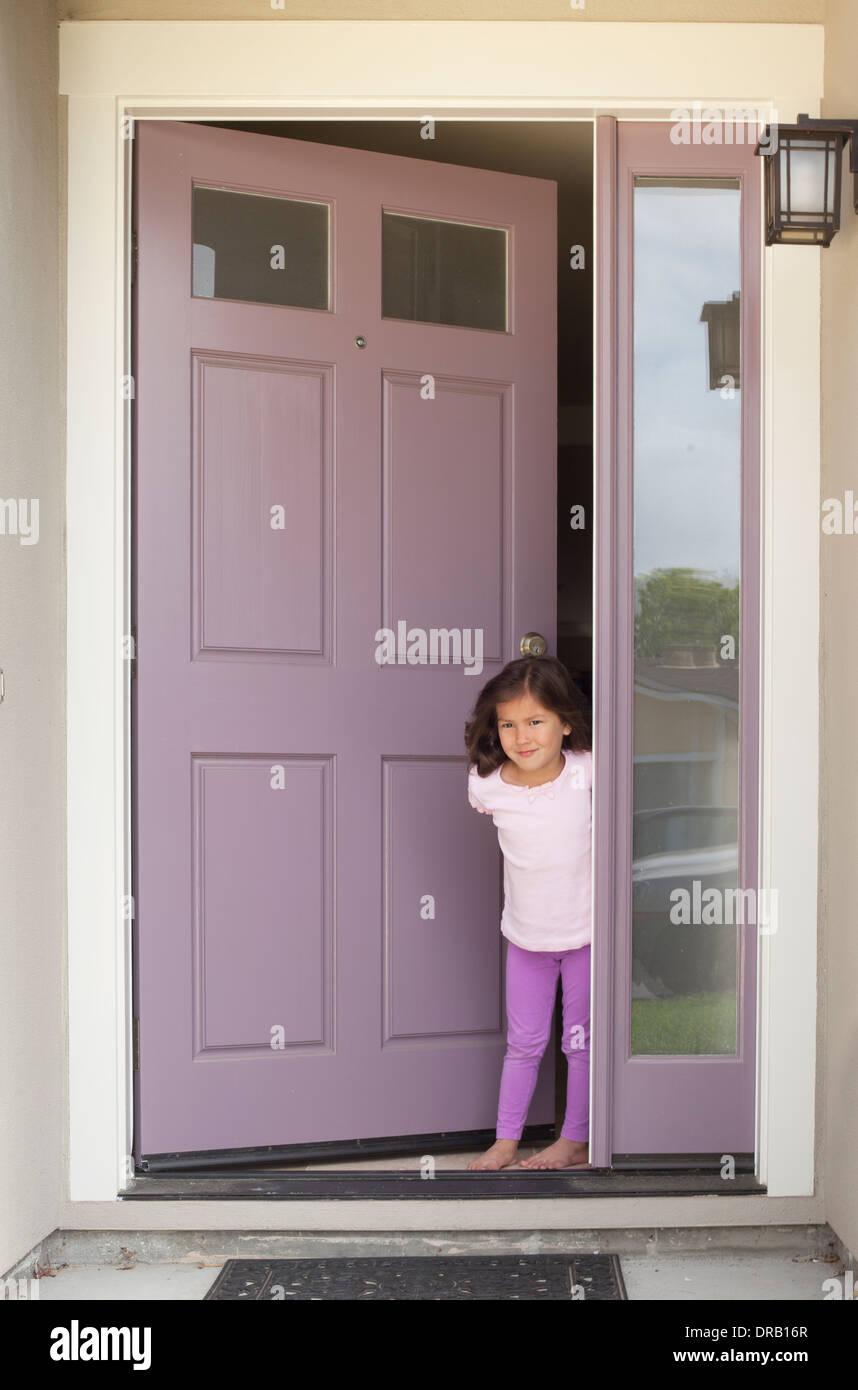 Petite fille avec porte ouverte à l'entrée de la maison Banque D'Images