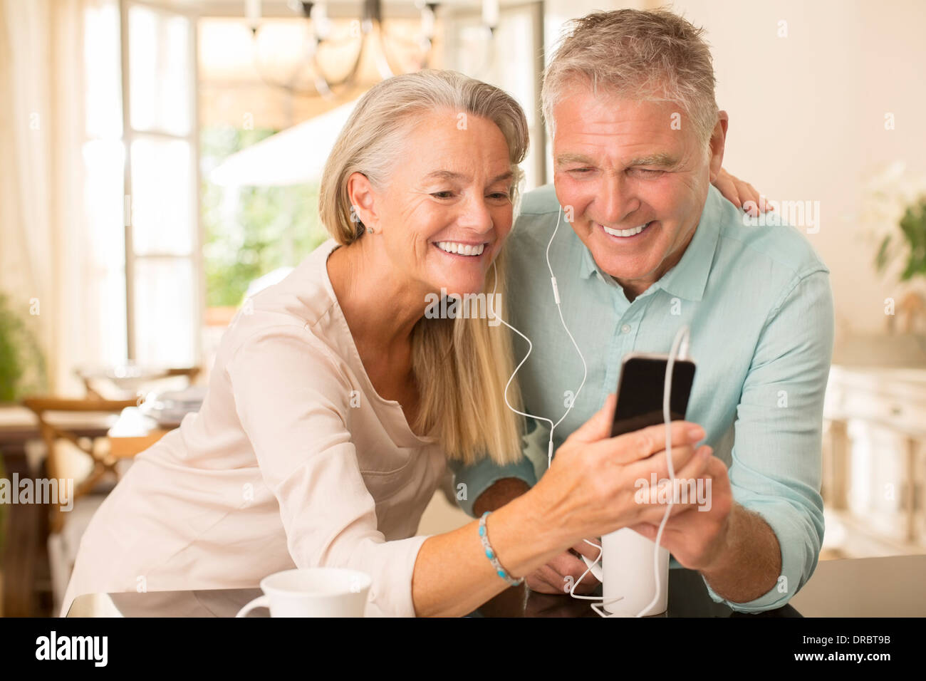 Senior couple partageant un lecteur mp3 dans la cuisine domestique Photo Stock