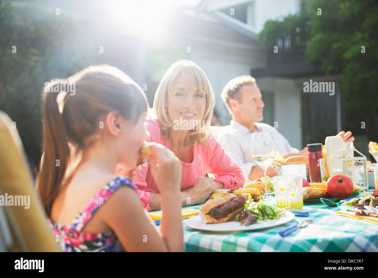 Family eating lunch at table patio Photo Stock