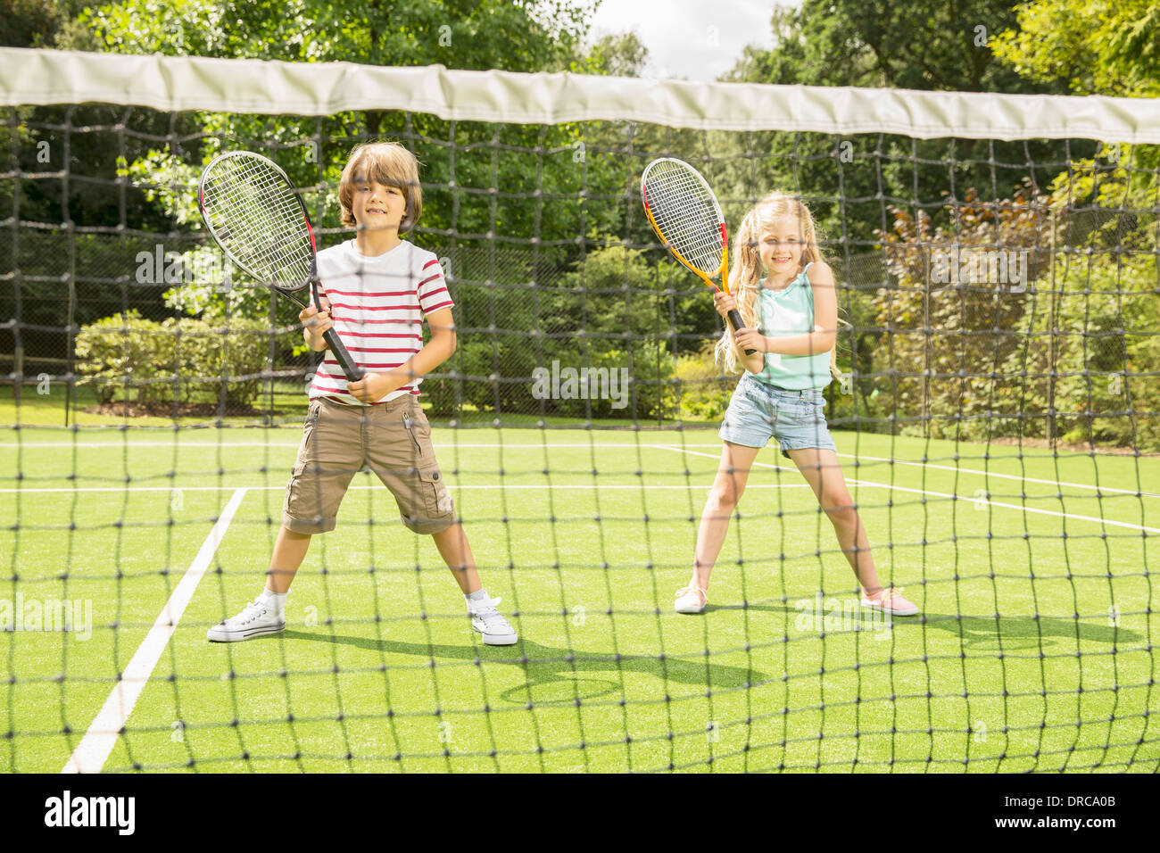 Enfants jouant au tennis sur gazon Photo Stock