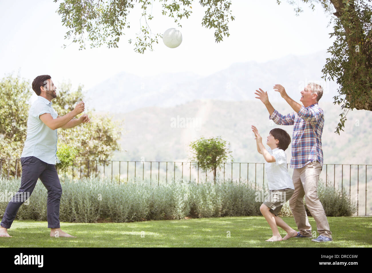 Multi-generation family playing volleyball in backyard Photo Stock