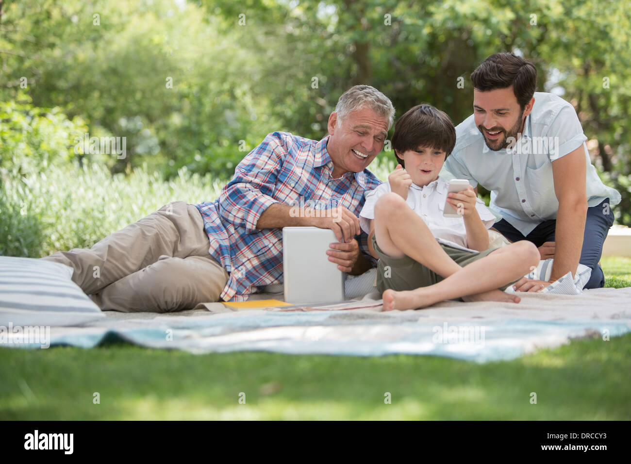 Multi-generation men with cell phone on blanket in grass Photo Stock
