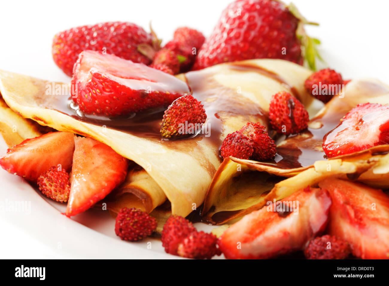 Des Crêpes avec sirop de chocolat avec fraises différentes on white Banque D'Images