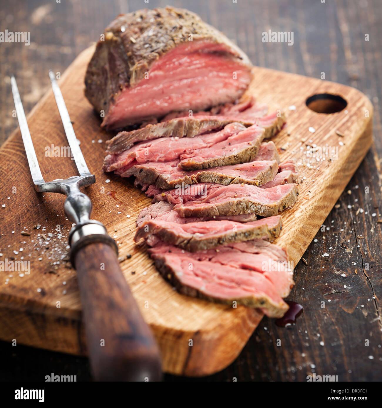 Rôti de boeuf sur une planche à découper et fourchette à viande Photo Stock