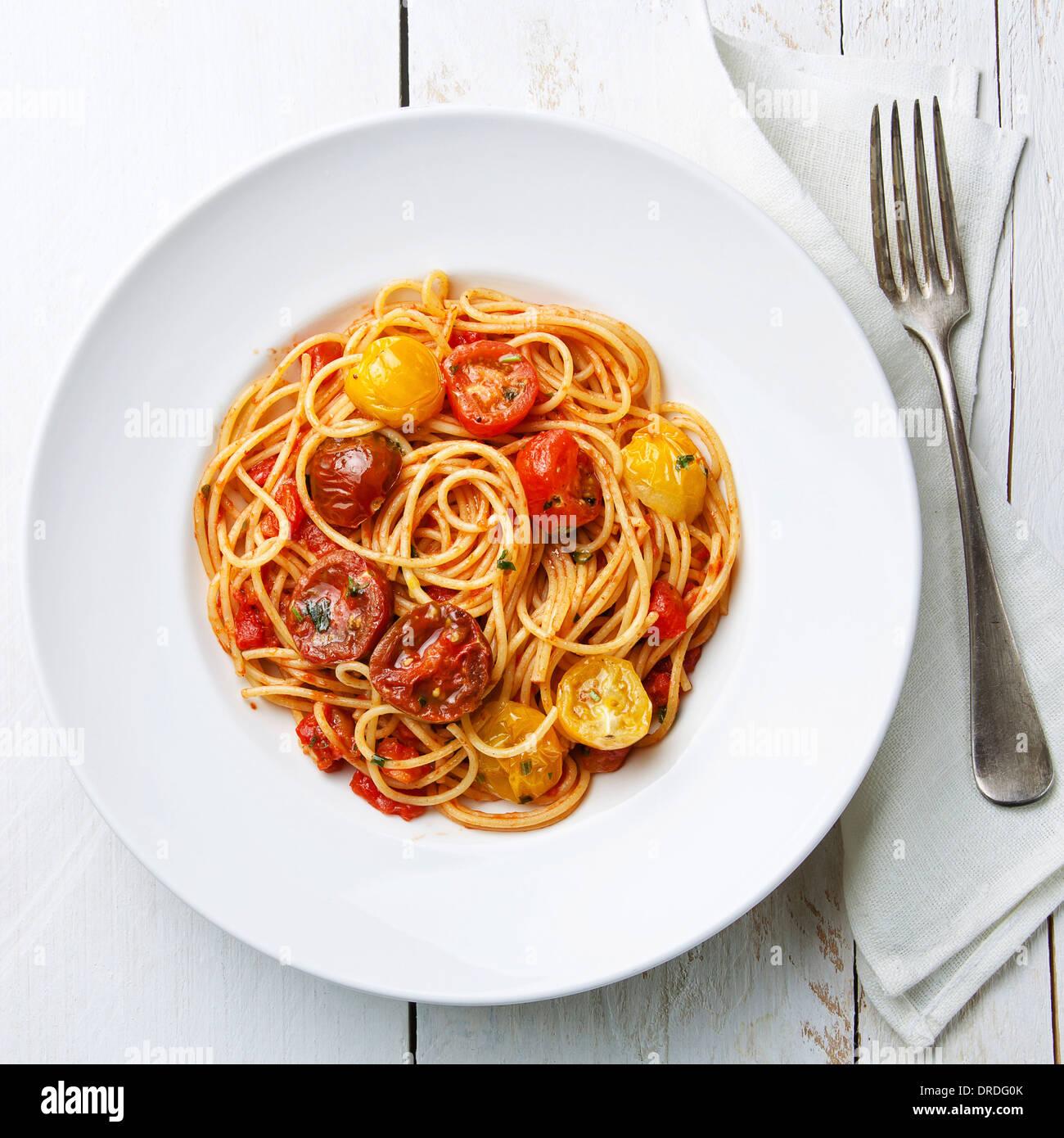 Spaghetti à la sauce tomate sur fond de bois blanc Banque D'Images