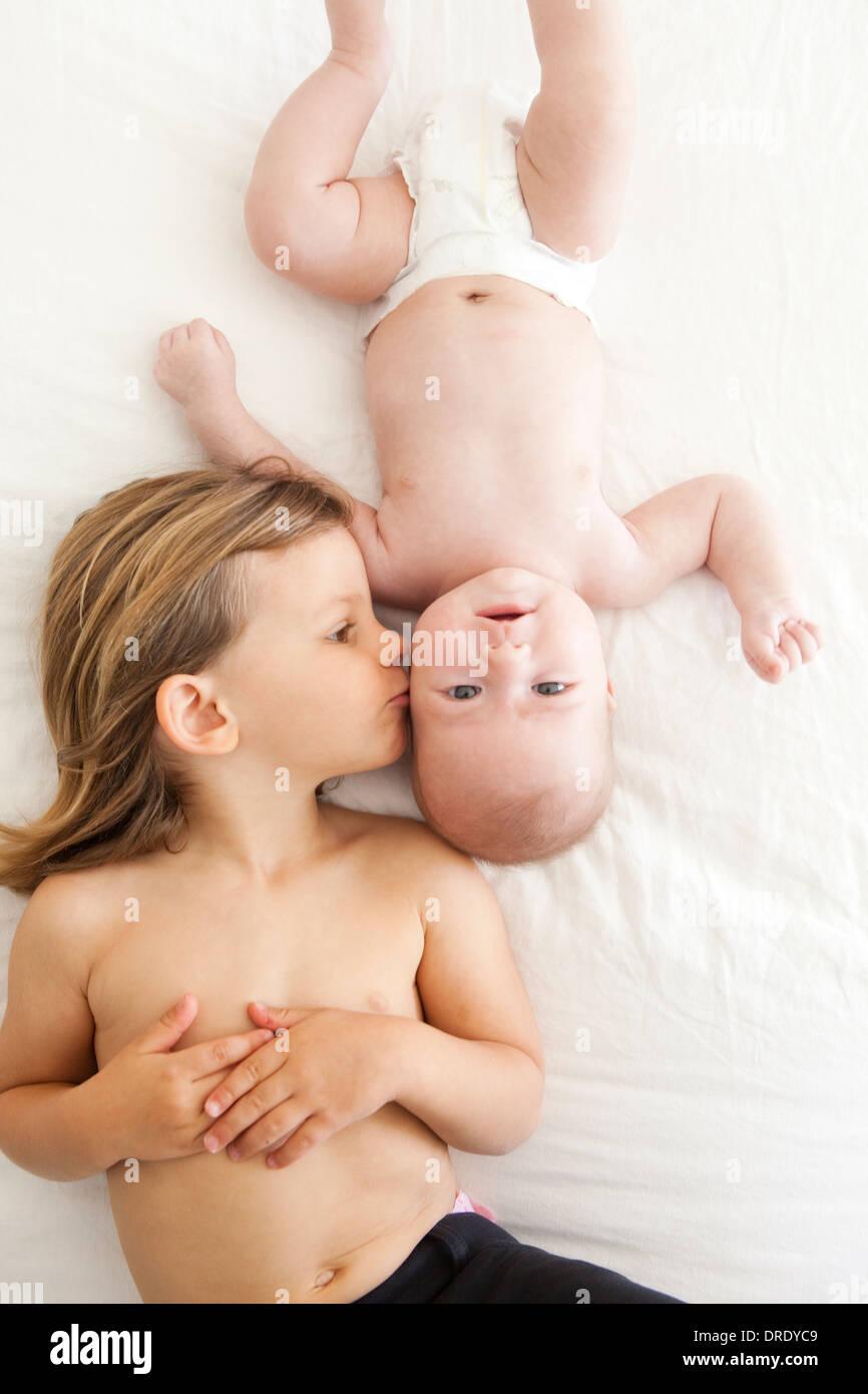 Soeur de l'embrasser plus jeune enfant Photo Stock