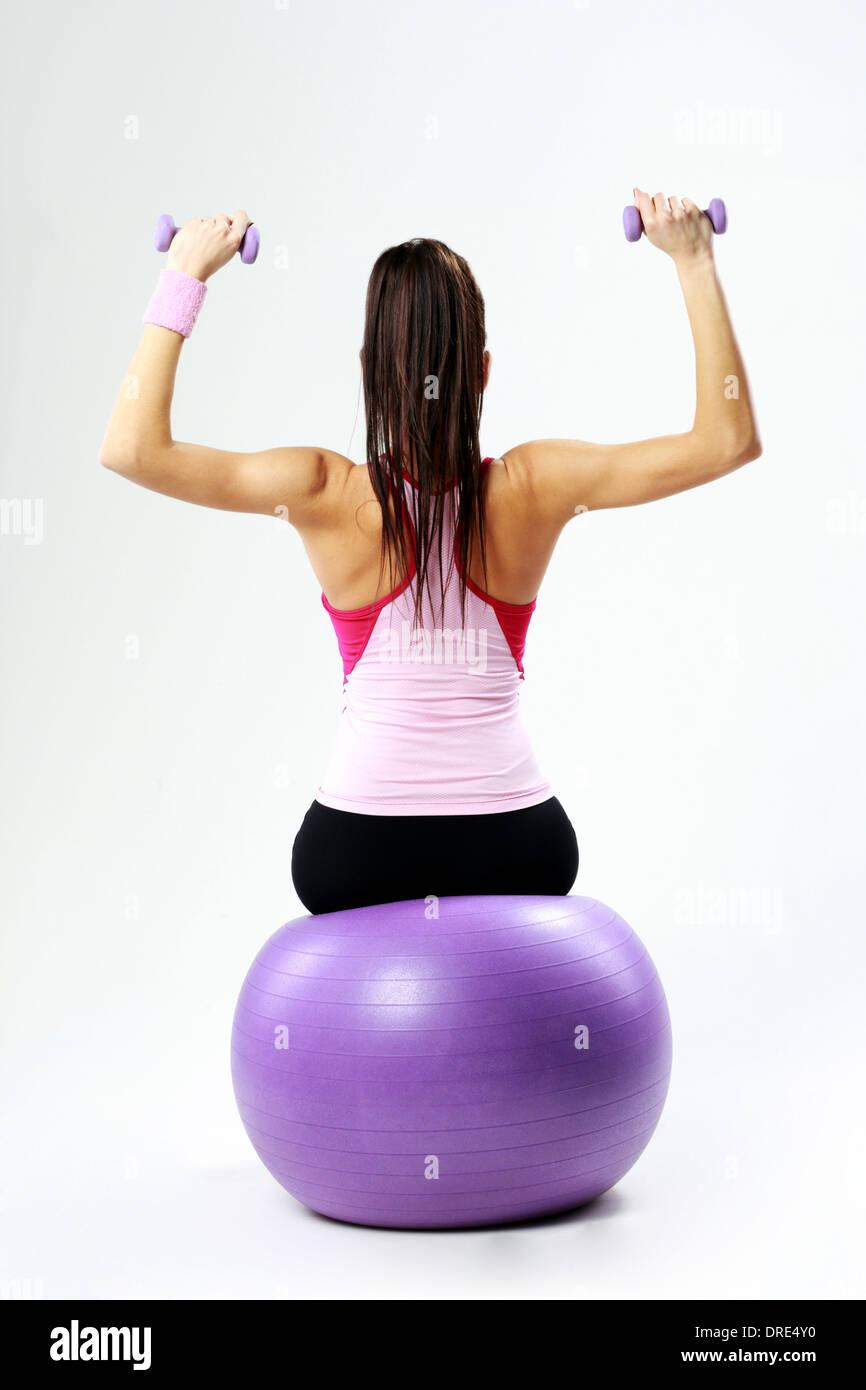 Vue arrière d'une jeune femme assise sur le sport fitball avec haltères sur fond gris Photo Stock