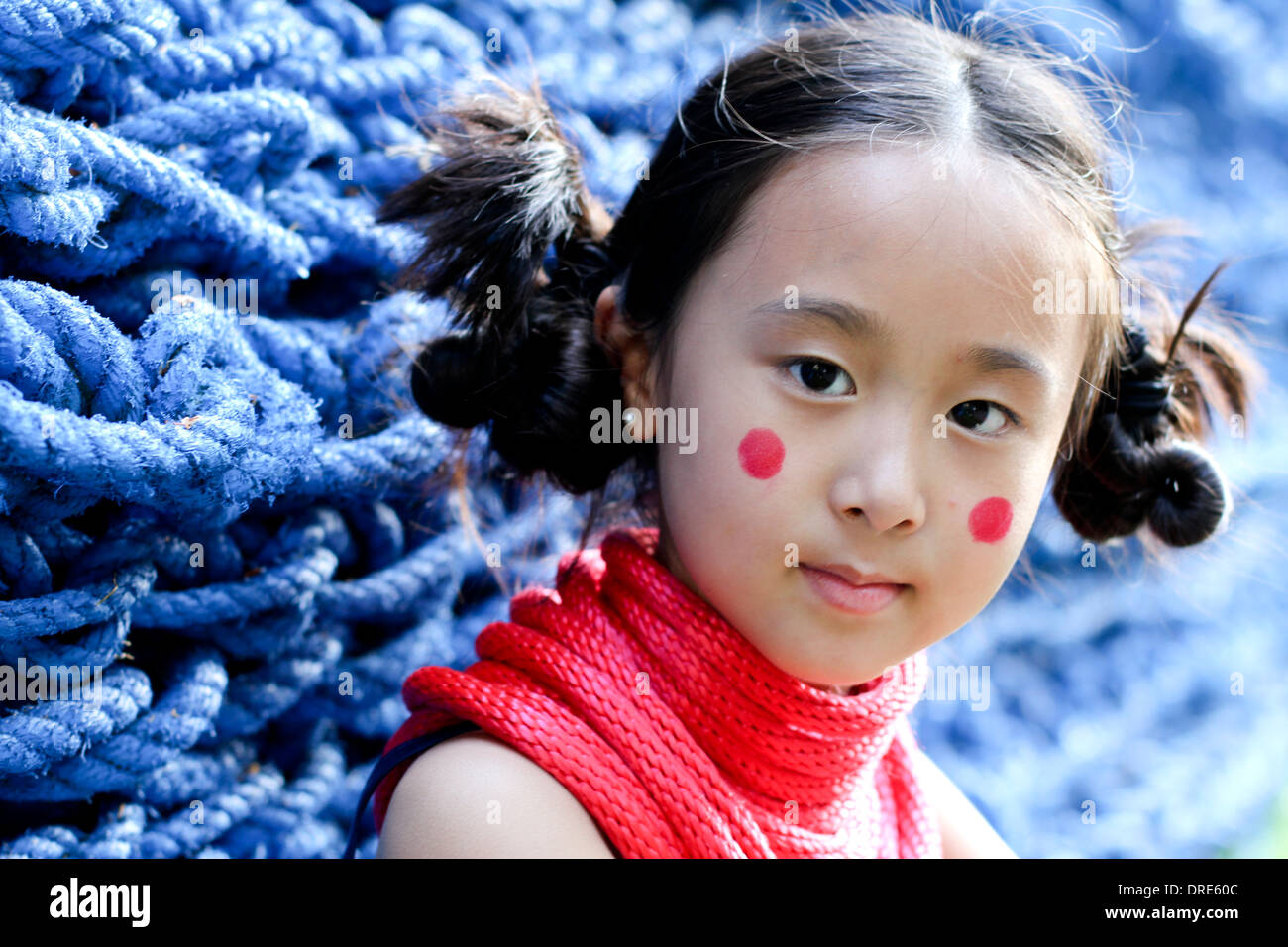 Asian girl en face du mur de corde bleu Photo Stock