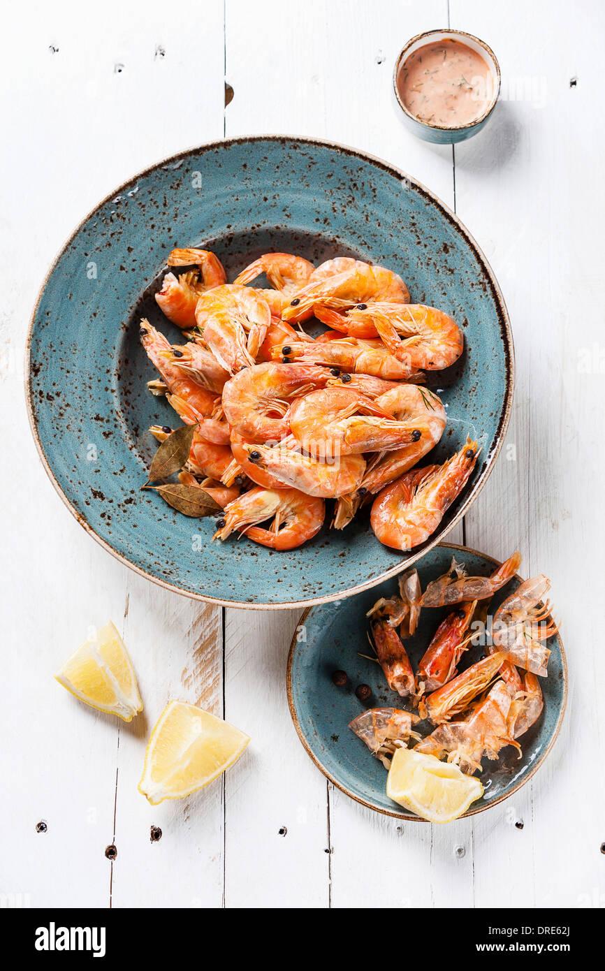 Les crevettes préparées sur plaque bleue sur fond de bois Photo Stock