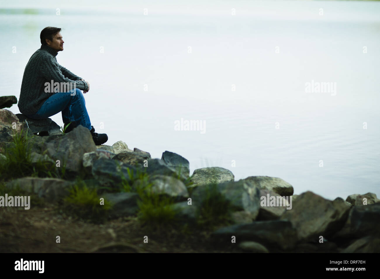 Colorado USA middle-aged man sitting on rocks looking pensive Photo Stock