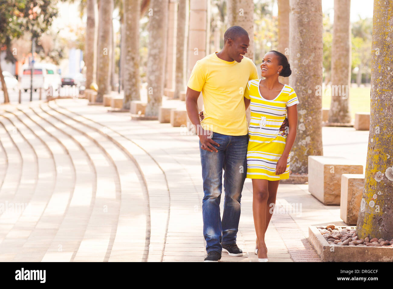 Cheerful young afro American couple walking on urban street Photo Stock