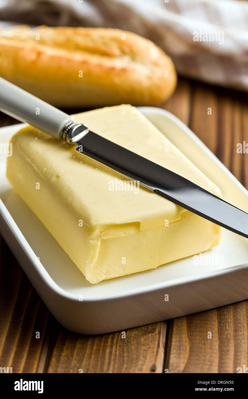 Cube de beurre à l'aide d'un couteau sur la table en bois Photo Stock