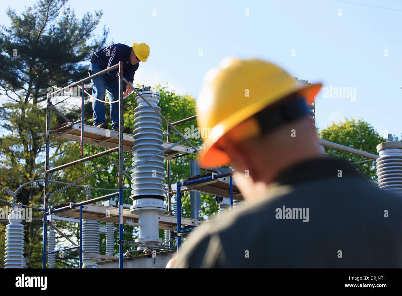 Ingénieur d'effectuer des opérations de maintenance sur l'isolateur haute tension remplis de liquide, Braintree, Massachusetts, USA Photo Stock