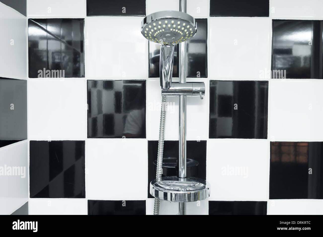 Tête de douche moderne dans une salle de bains avec carrelage noir ...