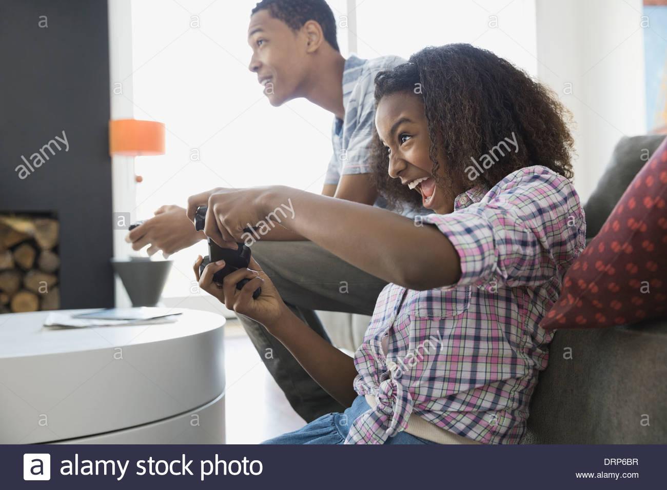 Frères et sœurs à jouer à des jeux vidéo à la maison Photo Stock