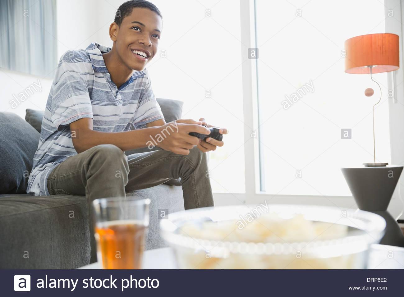 Jouer à des jeux vidéo de l'adolescence à la maison Photo Stock