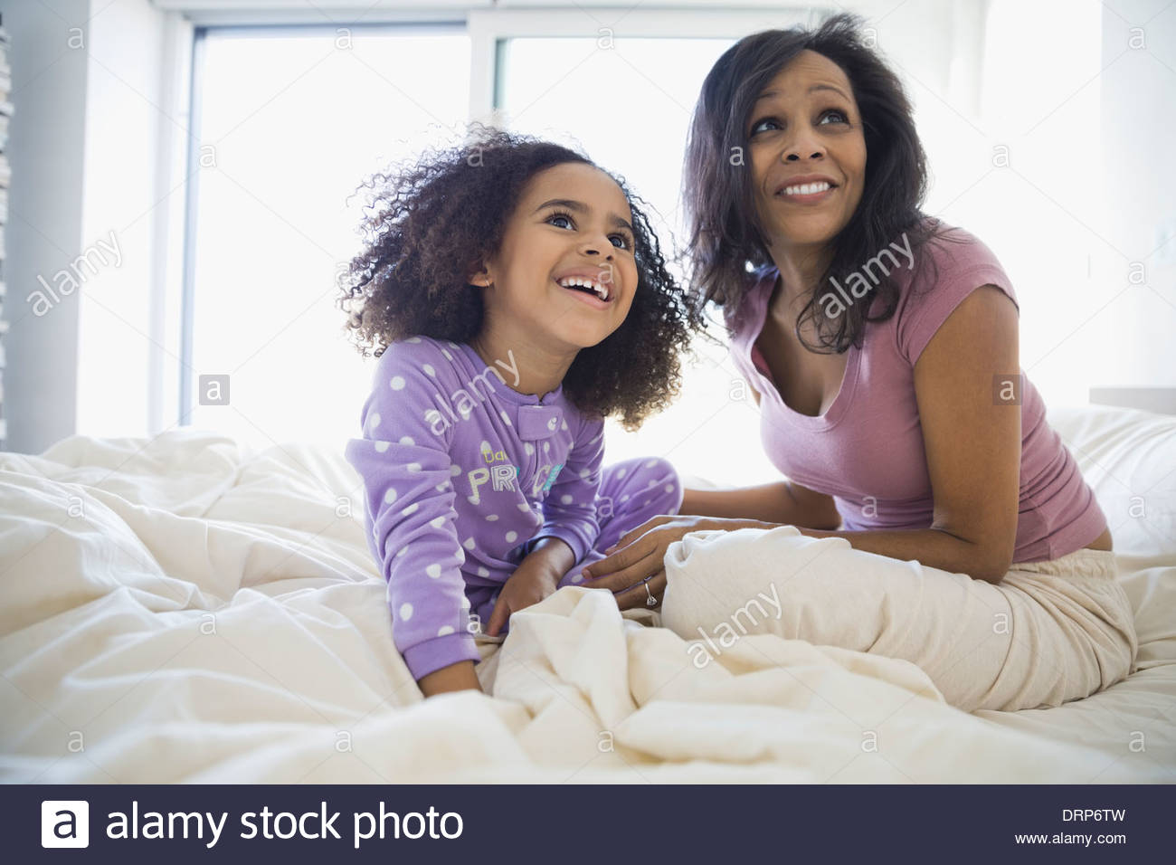 Smiling mother and daughter sitting on bed Photo Stock