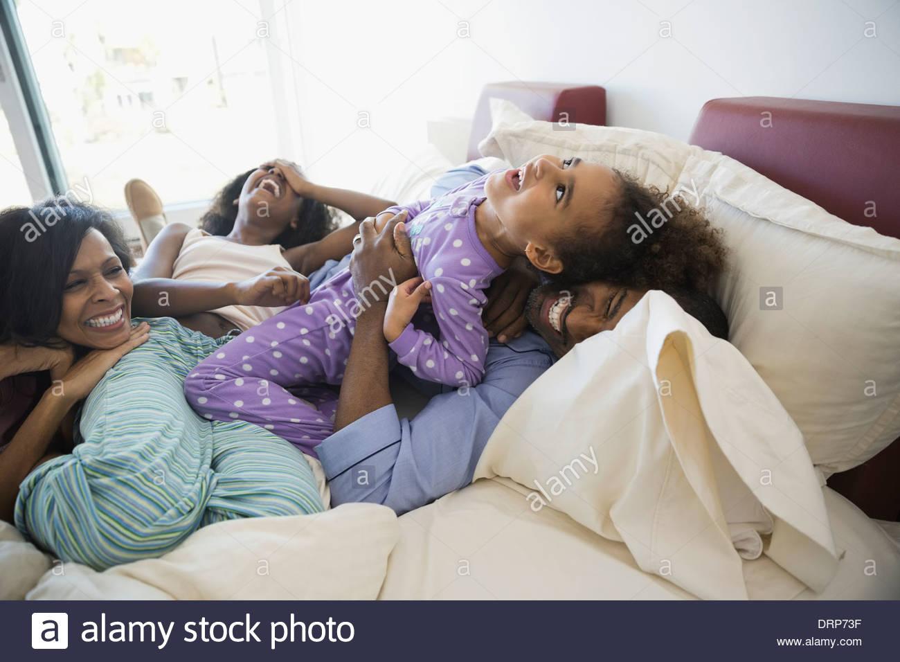 Famille ludique au lit Banque D'Images