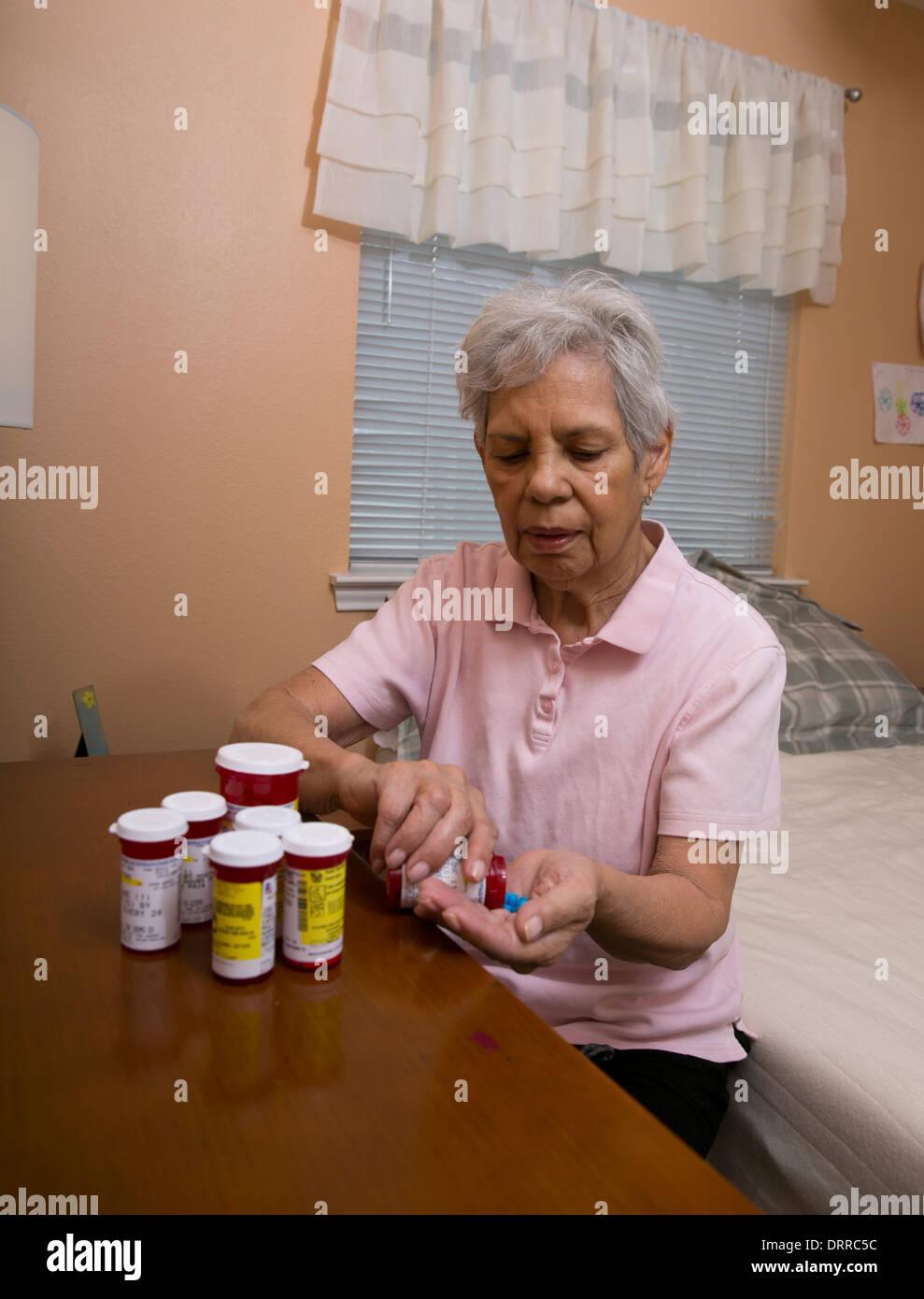75 ans Senior citizen femme hispanique organise ses multiples médicaments comprimés alors qu'à la maison Photo Stock