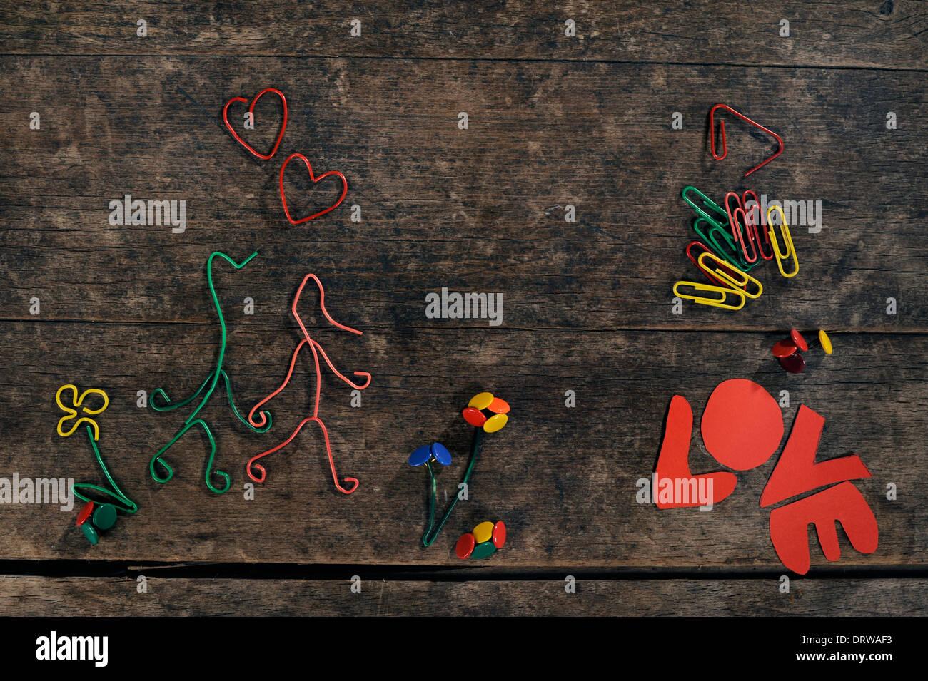 Histoire d'amour créatif, en couple dans l'amour, coeurs et fleurs fabriqué à partir de trombones et punaises sur un beau fond de bois. Photo Stock