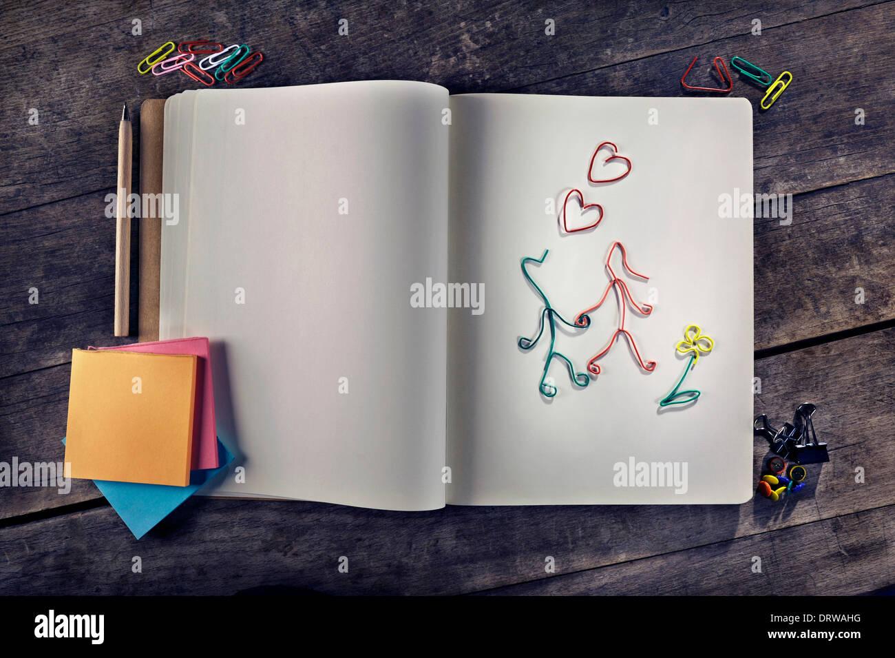 Messages d'amour en utilisant deux personnalisables lovers fabriqué à partir de trombones, vierge, vierge de l'ordinateur portable vintage post-it sur fond de bois. Photo Stock