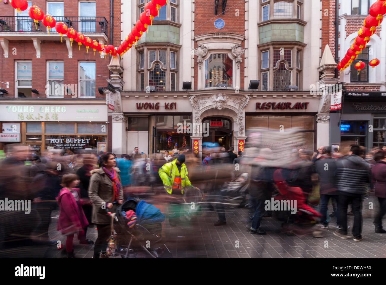 Chinatown, Londres, Royaume-Uni. 2 février 2014. Un homme recueille des foules comme litière passe devant lui par dans le quartier chinois alors qu'ils célèbrent l'année du cheval Photo Stock