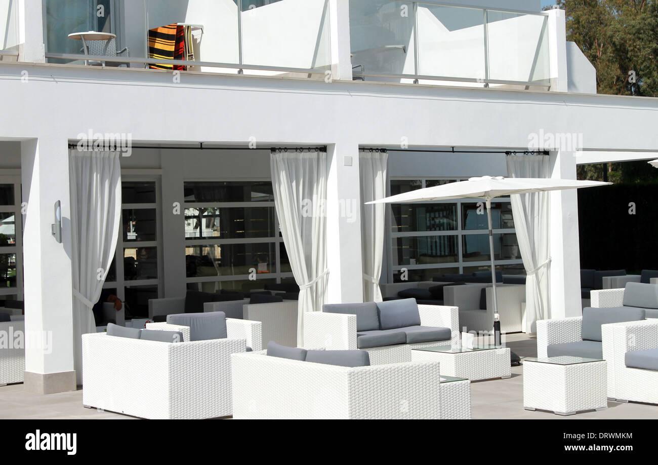 Patio à l'extérieur de l'hôtel de luxe avec des chaises et canapés. Photo Stock