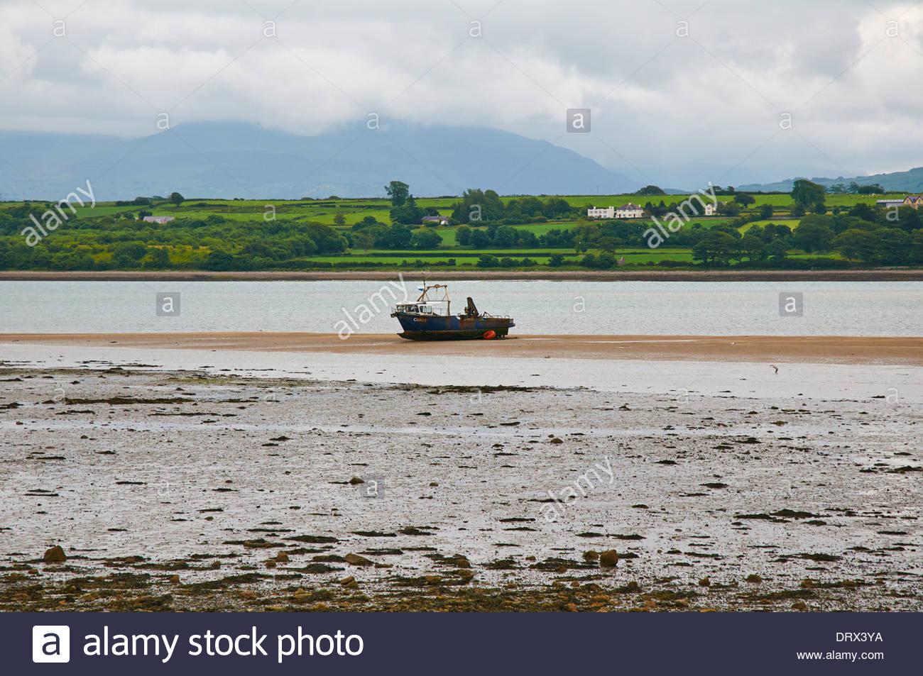 Bateau de pêche chalutier sur banc de sable lors de la marée est sur le détroit de Menai, sur l'île d'Anglesey ynys Banque D'Images
