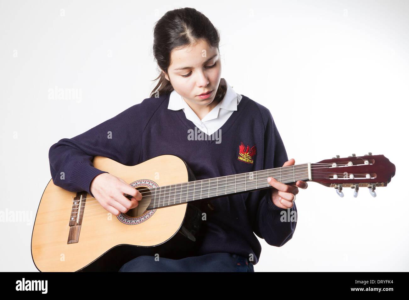 Teenage schoolgirl joue la guitare acoustique Photo Stock