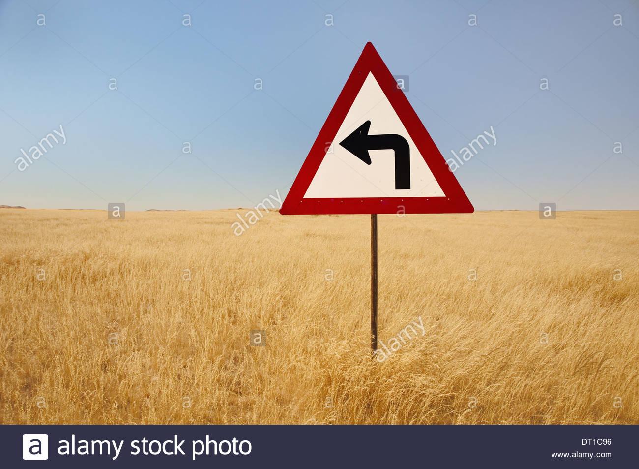 La Namibie, tourner à gauche au panneau de circulation hautes herbes Namibie Photo Stock