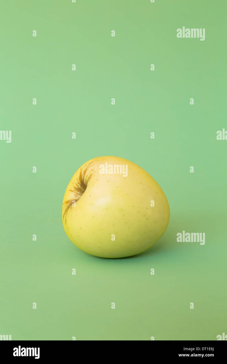 Seule pomme Golden Delicious sur fond vert Photo Stock
