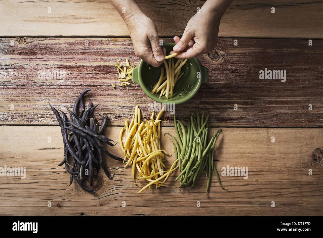 Jaune et Noir vert bio haricots Légumes frais étant en tête et queue par une personne avant de cuisiner Photo Stock