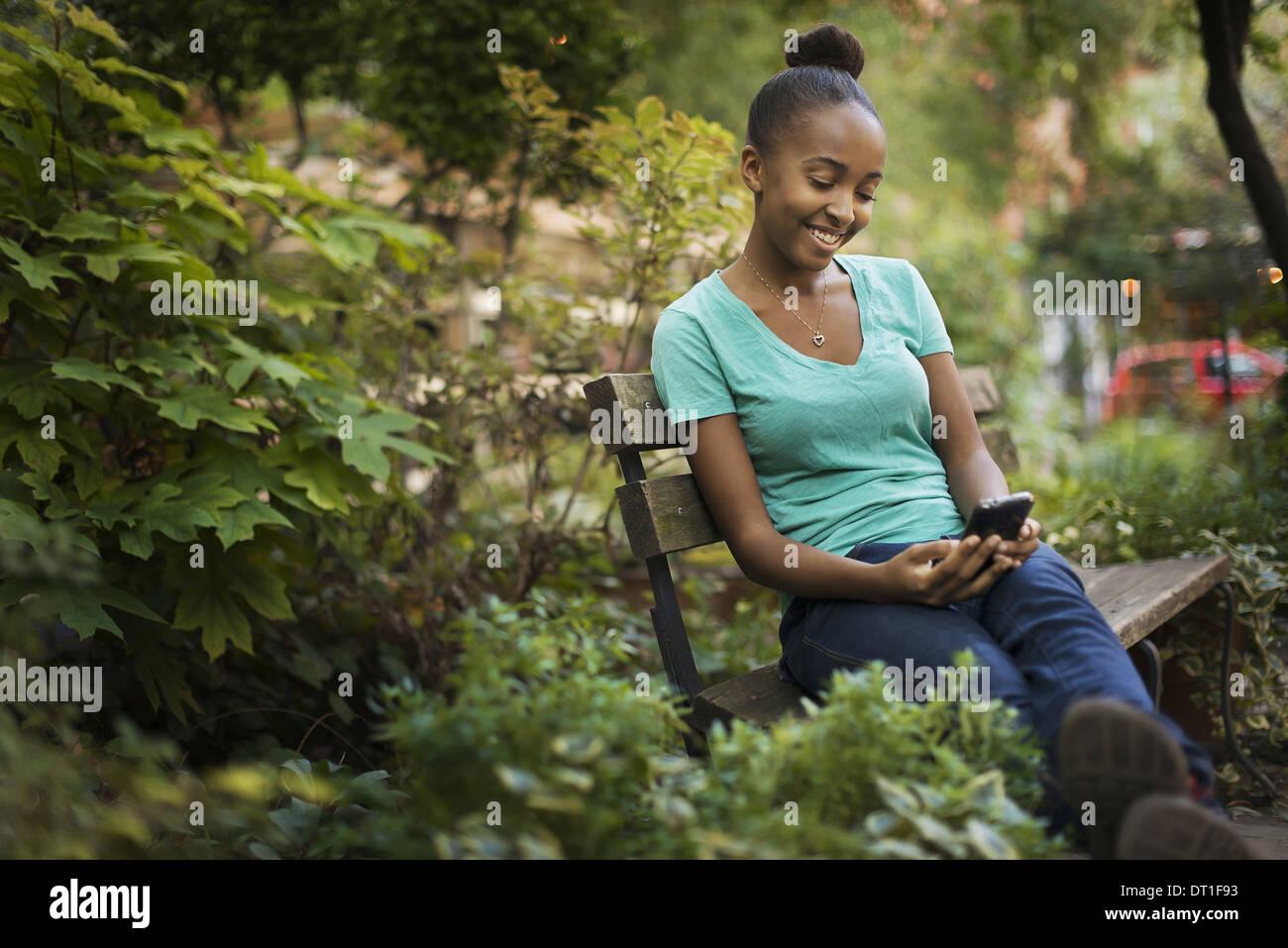 Une jeune adolescente assise sur un banc à l'écran à un pad ou texting Photo Stock