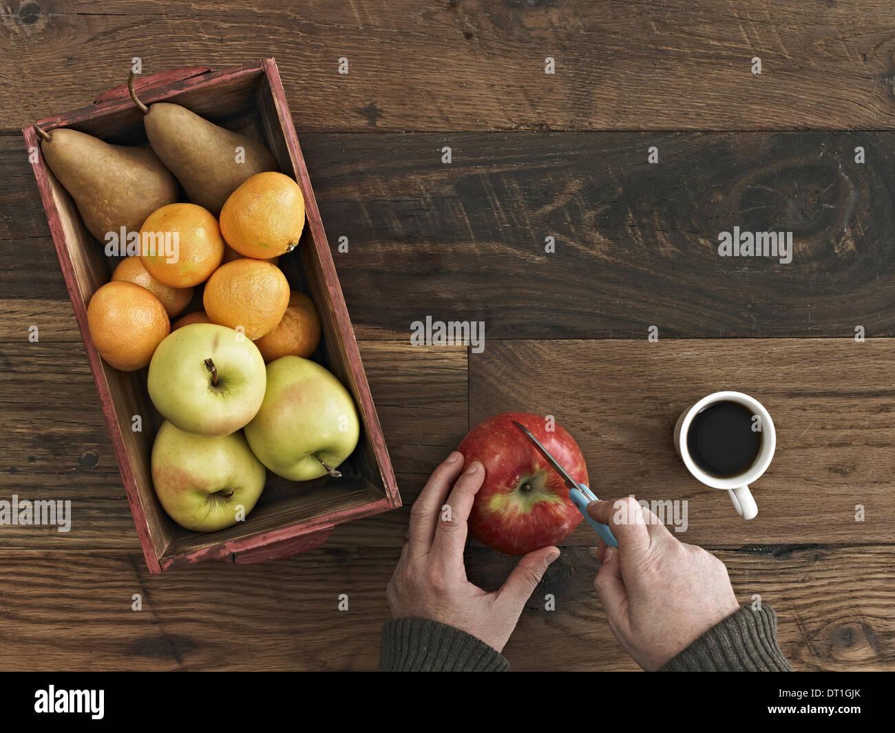 Une table en bois haut de gamme d'un bois fort de fruits frais les poires et les oranges une personne coupant une pomme Banque D'Images