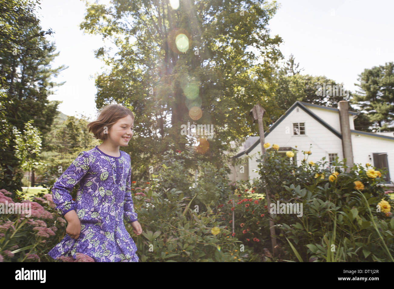 Un enfant dans une robe bleu à motifs qui traverse un jardin maison Photo Stock