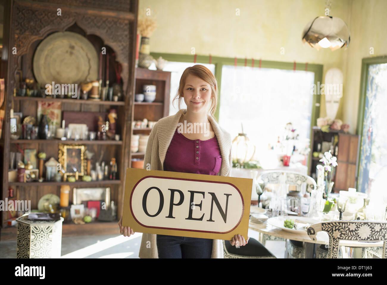 Une femme debout dans un magasin d'antiquités brandissait une inscription affiche des marchandises tout autour d'elle Photo Stock