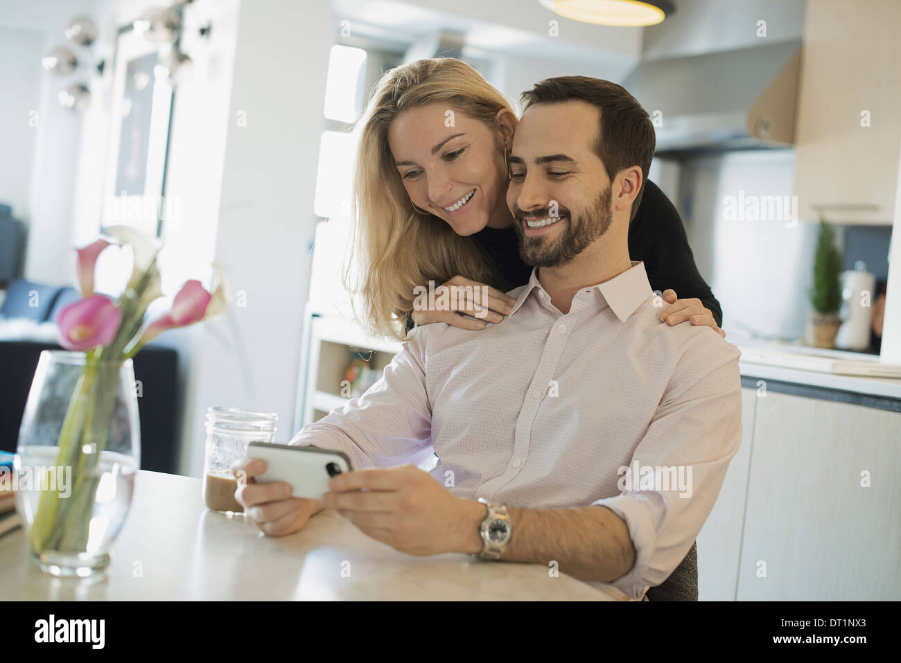 Couple à la maison regarder des images sur smartphone Photo Stock