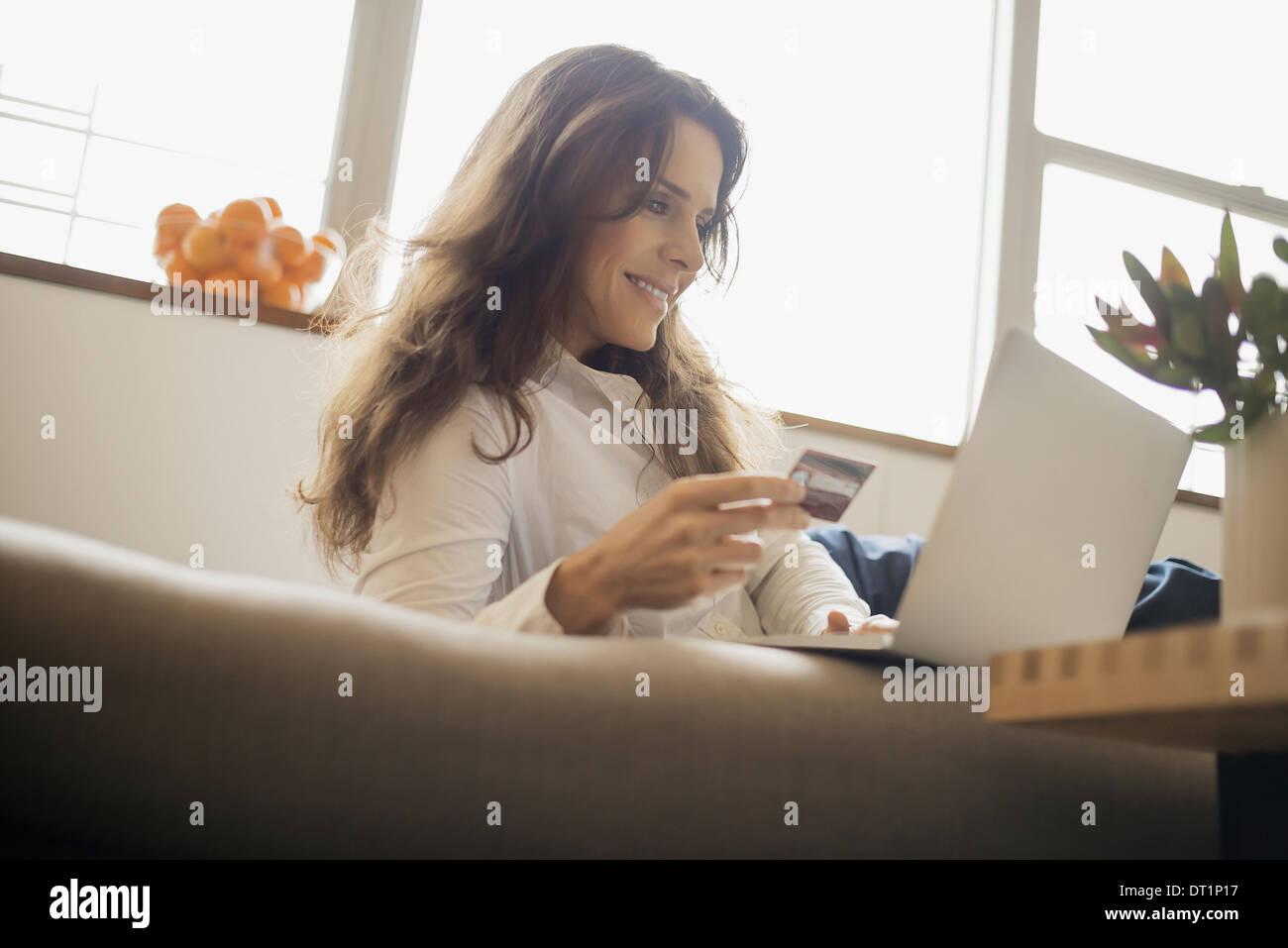 Femme du magasinage en ligne sur ordinateur portable sur canapé avec carte de crédit Photo Stock