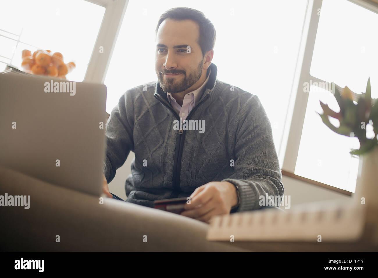 L'homme du magasinage en ligne sur ordinateur portable sur canapé avec carte de crédit Photo Stock