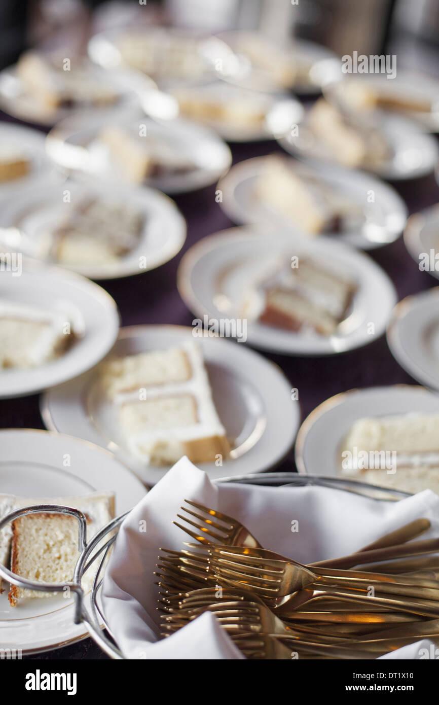 Une table chargée de chine et Blanc plaques un panier plein de fourchettes dessert une tranche de gâteau de mariage Photo Stock