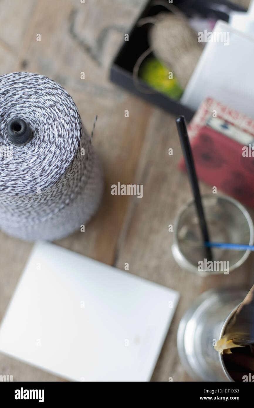 Une table avec un petit groupe d'objets Tankard et crayons de papier et une grande boule de ficelle Photo Stock