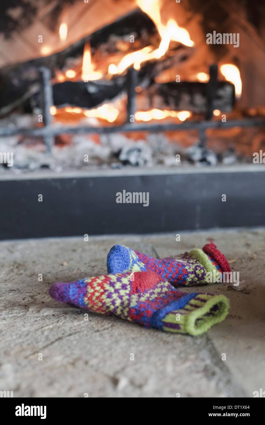 Un feu de bois dans un foyer rougeoyant avec cœur et les flammes en tricot gants de laine à motifs Photo Stock
