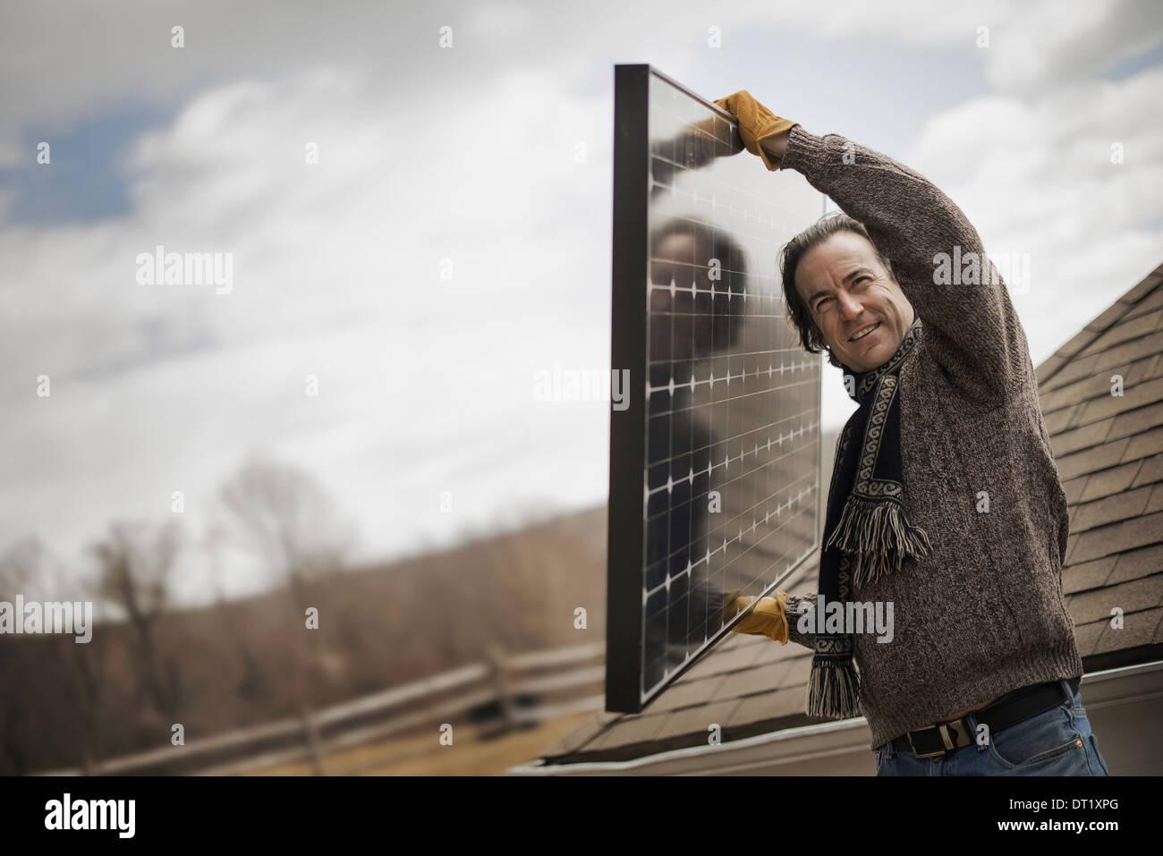 Un homme portant un grand panneau solaire à l'échelle d'une ferme Photo Stock