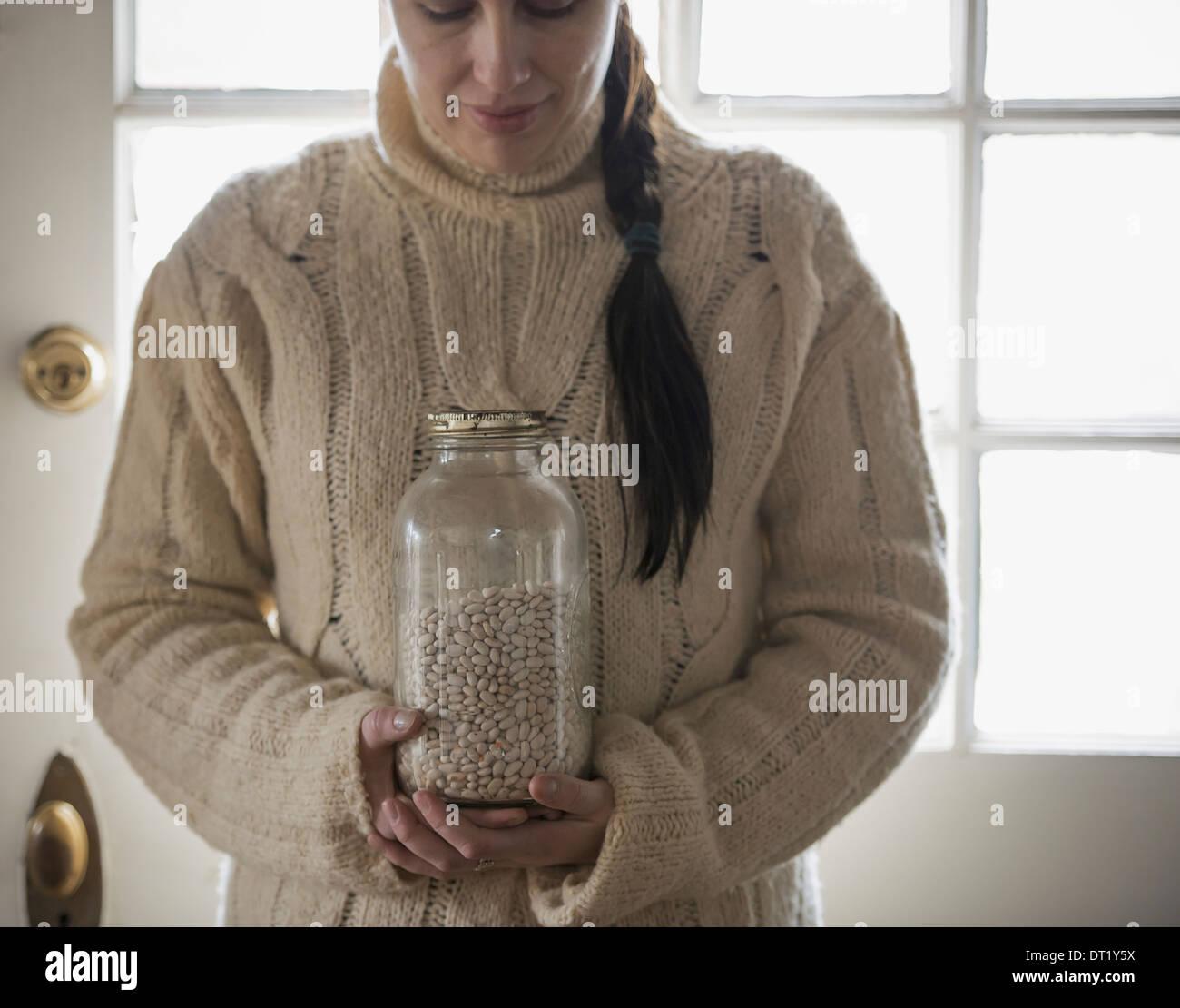 Une femme dans un chandail en tricot câble tenant un verre pot de haricots blancs Photo Stock